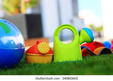 Two colorful watering cans for children in the summer. Towel in the background, piece of paddling pool on the left. Low depth of field.