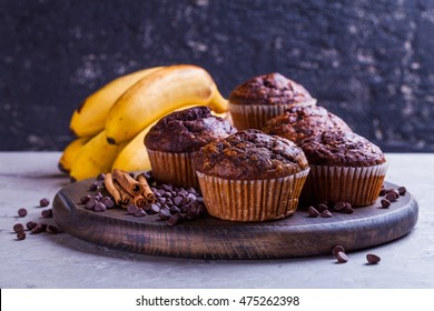 Two colors chocolate-banana muffins on the wooden board. Copy space photo. Fresh bananas near it.