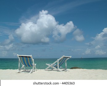 Two colourful deckchairs on a tropical island