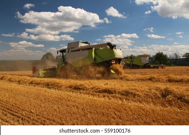 Two combines in barley field, one in background, summer harvest, blue sky with clouds, side perspective