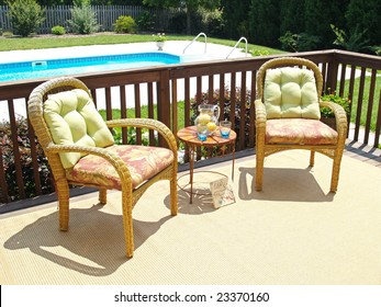 Two comfortable chairs on a patio overlooking a pool in the backyard
