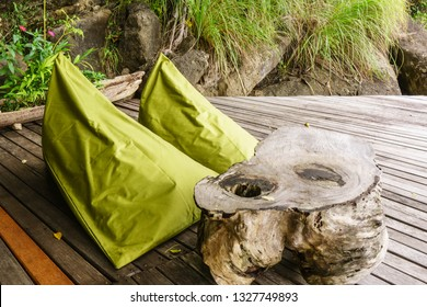 Two comfortable slouchy green beanbags and a carved wooden table on a weathered wooden deck at the base of a rocky cliff.