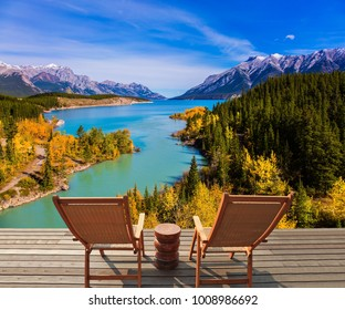 Two comfortable wooden deckchairs by the Abraham lake. Warm autumn in the mountains of Canada. Concept of ecological and active tourism