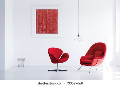 Two comfy red armchairs placed in bright room with abstract painting and wastebasket