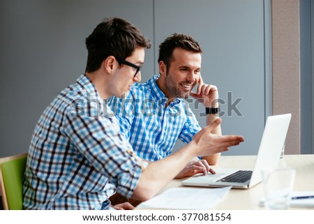 Two computer geeks discussing new project on laptop