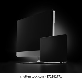 two computers with black screen on a dark background