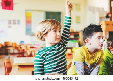 Два концентрированных 4-5 летних мальчиков в классе, ребенок поднимает руку на уроке