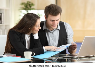 Two concentrated coworkers checking paper informs together at office