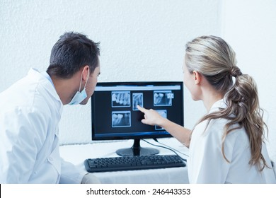 Two concentrated dentists looking at x-ray on computer
