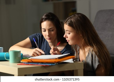 Two concentrated students studying together commenting notes at home late hours