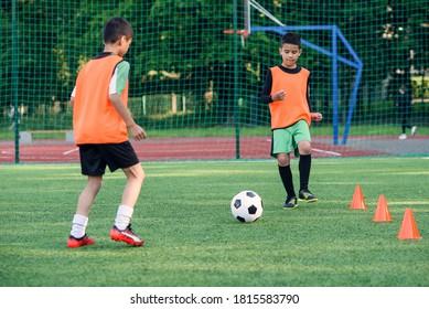 Zwei konzentrierte Teenager übergeben sich im Fußballstadion. Teamwork und gemeinsames Schulungskonzept.