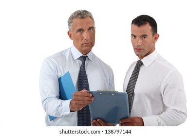 Two concerned businessmen stood with clip board
