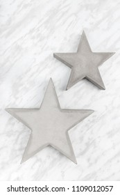 Two concrete stars on marble background. Modern decor.