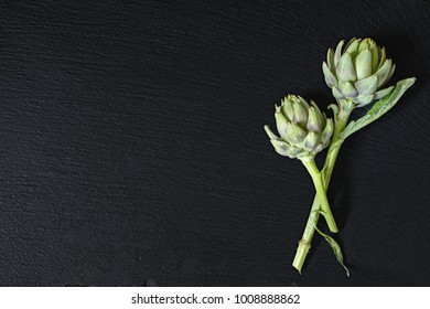 Two cones fresh green artichoke on a black stone surface.  Top view, copy space. Healthy eating concept.
