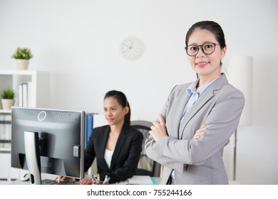two confidence successful office women working together like a team and cross arms face to the camera.