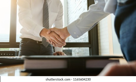 Two confident business man partner shaking hands in meeting room