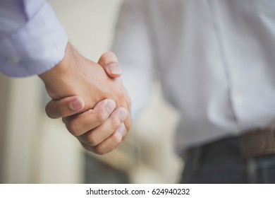 Two confident business man shaking hands to seal a deal with his partner after finishing up a meeting,