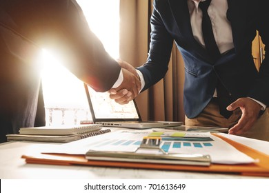 Two confident business man shaking hands during a meeting in the office, success, dealing, greeting and partner in sun light