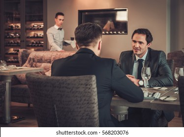 Two confident business men have business lunch at restaurant.