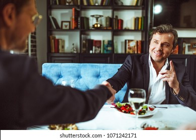 Two confident businessman shaking hands at restaurantafter signing agreement.