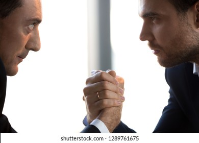 Two confident businessmen compete arm wrestling looking in eyes showing power, armwrestling as business competition rivalry confrontation concept, fighting for leadership success, side close up view