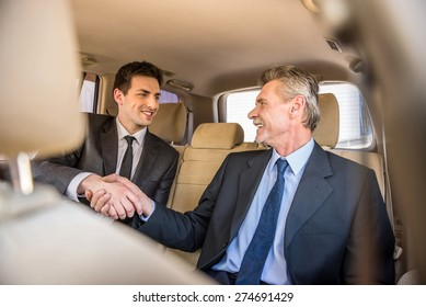 Two confident businessmen shaking hands and smiling while sitting in the car.