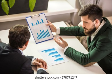 Two confident businessmen in suits working on project at business lunch and looking at chart.
