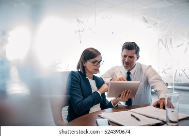 Two confident businesspeople using a digital tablet together while working at a table in a modern office