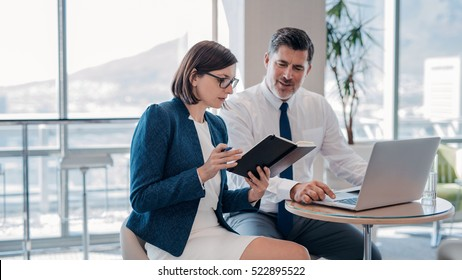 Two confident businesspeople using a laptop and reading notes together while working at a table in a modern office