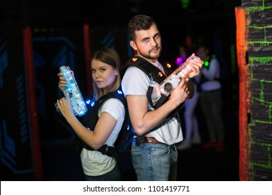 Two confident laser tag players standing back to back with guns on dark gaming arena