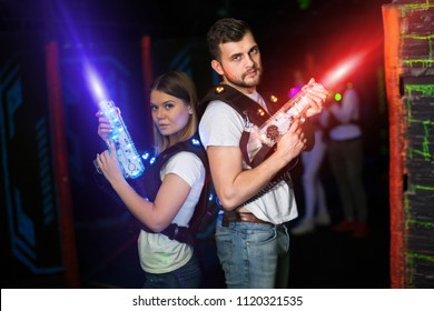 Two confident laser tag players standing back to back with guns on gaming arena in bright beams of laser gun