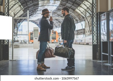 Two confident multi-ethnic bearded businessmans together wearing casual clothes and holding travel bags in hands waiting the train on the railway platform.