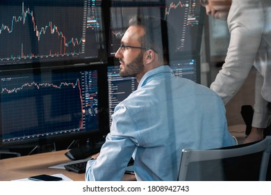 Two confident stock broker looking at display, analyzing global bitcoin price on network diagram and working together in office
