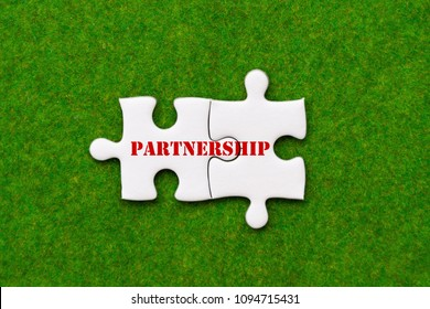 two connected jigsaw puzzle pieces with partnership woring