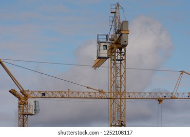 Two construction cranes of different sizes stand on construction site