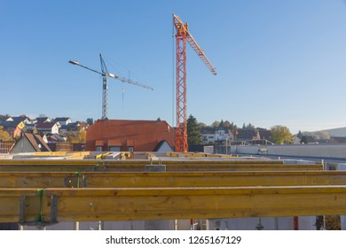 Two construction cranes at construction site in front of shell