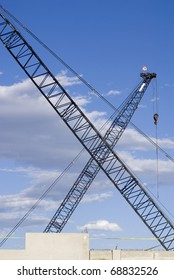Two construction cranes at a work site