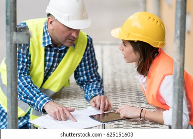Two construction engineers holding plans and inspecting the construction site among scaffolding