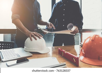 Two construction engineers working at  construction site with blueprint on table