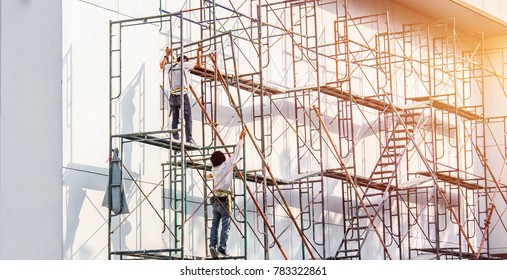 Two construction man working on scaffolding of a building and frame structure. Construction Zone