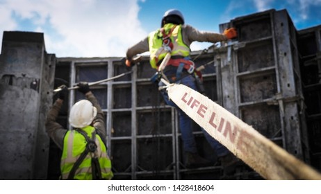 Two Construction workers connected with a safety harness to a life line system for builders
