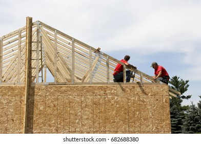 Two construction workers on the roof of a house being built.