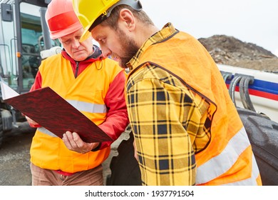 Two construction workers on the construction site of the house building control a building permit