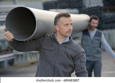 two construction workers on site holding pipe