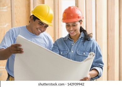 Two construction workers reading plans