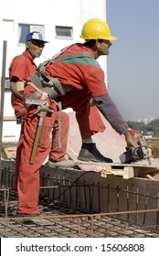 Two construction workers are working on the rooftop of an unfinished building. Vertically framed shot.