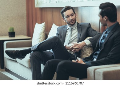 Two content adult business men sitting on couch and chatting in lounge with wall and abstract painting in background