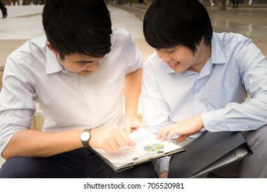 Two Content Business Partners Discussing Business Model With Paper Work