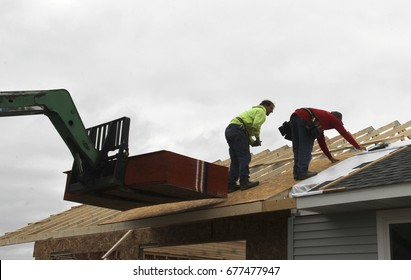Two contractors putting sheeting on a roof during construction