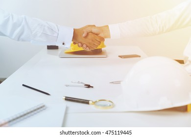 Two contractors shaking hands above white table with white hard hat and magnifying glass. Concept of sealing a deal.